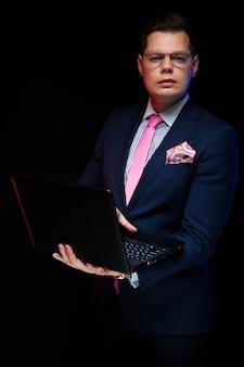 Porträt des überzeugten hübschen ernsten geschäftsmannes, der an dem laptop lokalisiert auf schwarzem arbeitet