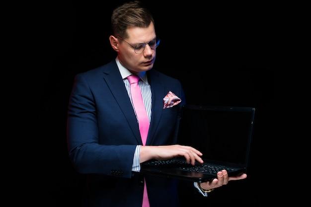 Porträt des überzeugten hübschen ernsten geschäftsmannes, der den laptop lokalisiert auf schwarzem hintergrund zeigt