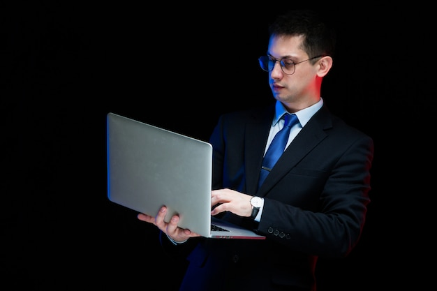 Porträt des überzeugten hübschen stilvollen geschäftsmannes, der laptop in seinen händen hält