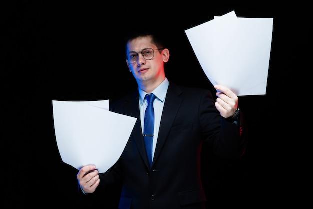 Porträt des überzeugten hübschen stilvollen geschäftsmannes, der papiere in seinen händen hält