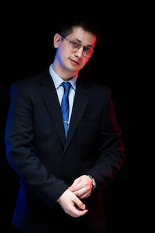 Porträt des überzeugten hübschen stilvollen geschäftsmannes mit der hand auf seinem anzug auf schwarzem hintergrund