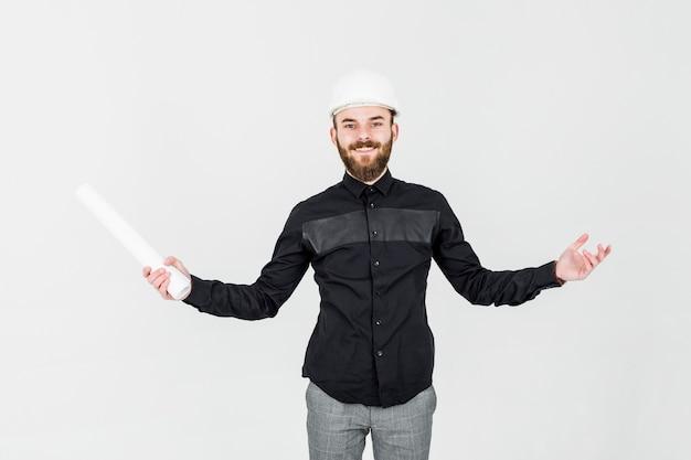 Porträt des überzeugten männlichen architekten, der plan gegen weißen hintergrund hält