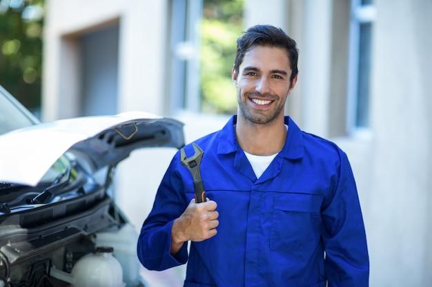 Porträt des überzeugten mechanikers schlüssel halten