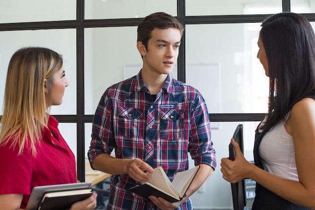 Porträt des überzeugten studentenjungen, der mit seinen freundinnen spricht