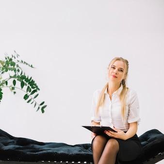 Porträt des überzeugten weiblichen psychologen, der auf der couch hält klemmbrett sitzt