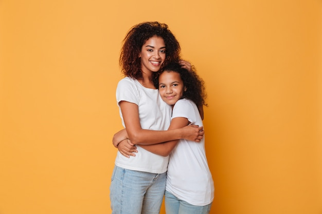 Porträt des umarmens mit zwei glücklichen afrikanischen schwestern