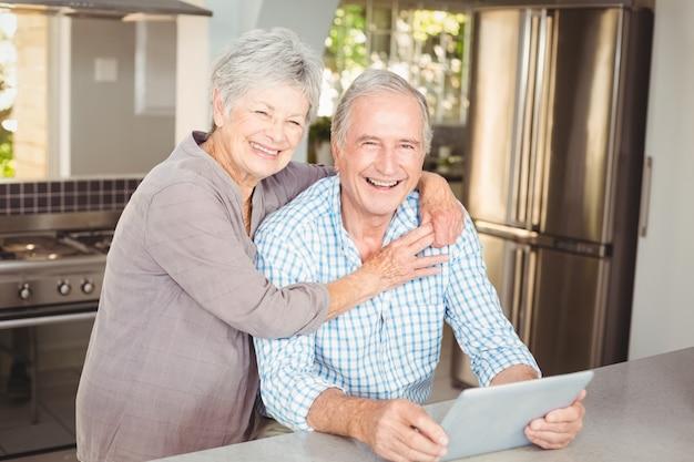 Porträt des umfassungsmannes der glücklichen älteren frau mit tablette