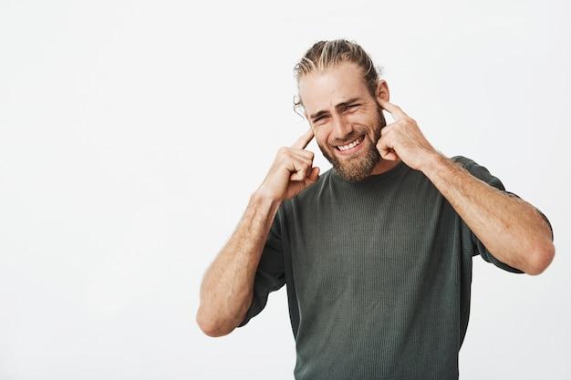 Porträt des unglücklichen bärtigen mannes, der ohren mit den fingern mit genervtem ausdruck schließt
