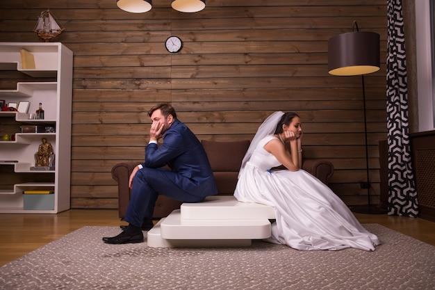 Porträt des unglücklichen familienpaares, das auf dem tisch auf holzraum sitzt