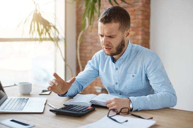 Porträt des unglücklichen reifen bärtigen buchhalters, der im firmenbüro arbeitet