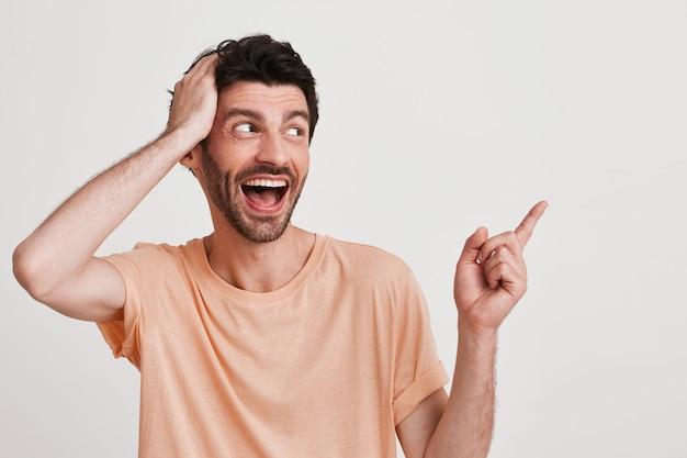 Porträt des unglücklichen unzufriedenen jungen mannes mit der borste trägt pfirsich-t-shirt sieht verärgert aus und zeigt zur seite mit finger auf weiß isoliert