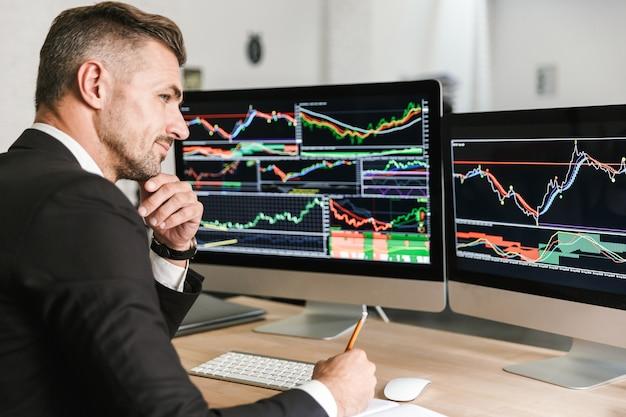 Porträt des unrasierten geschäftsmannes 30s, der anzug trägt, der im büro arbeitet und auf computer mit grafiken und diagrammen am bildschirm schaut