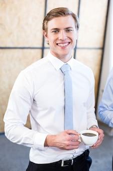 Porträt des unternehmensleiters, der eine tasse tee im büro isst