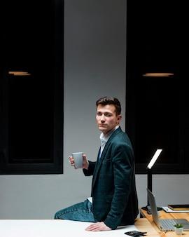 Porträt des unternehmers, der kaffee nachts trinkt
