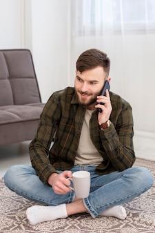Porträt des unternehmers, der von zu hause aus am telefon spricht