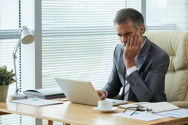 Porträt des unternehmers von mittlerem alter, der über bankrott mit frustrierter geste herausfindet