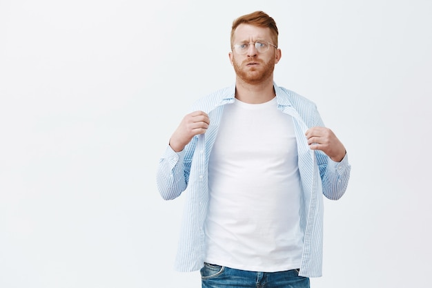 Porträt des unzufriedenen, der unter sommerwetterwetter-mann mit roten haaren und bart in der brille leidet, hemd wickelt, um körper zu kühlen, von hitze ausatmen