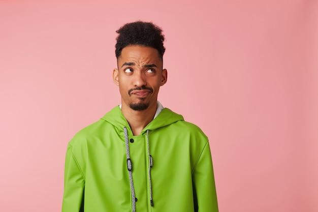 Porträt des unzufriedenen jungen afroamerikanischen gutaussehenden mannes im grünen regenmantel, steht, fragt fragend zum kopienraum auf.