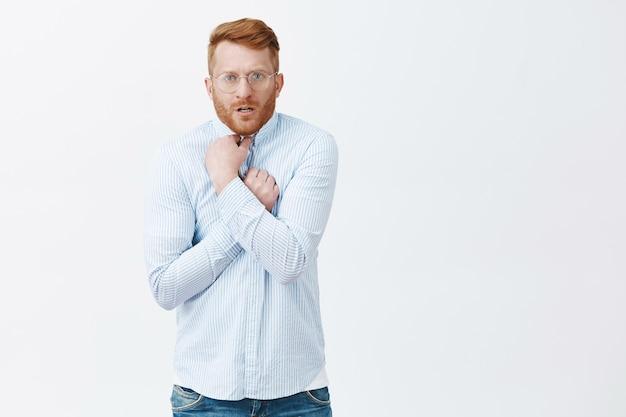 Porträt des unzufriedenen verlegenen und intensiven rothaarigen kerls mit borste in der brille, die hemd auf brust zieht