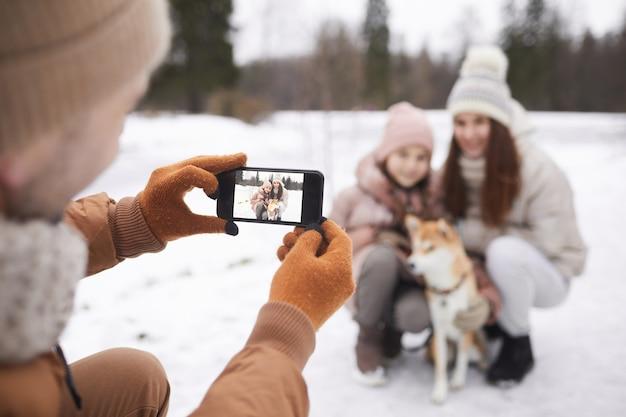 Porträt des vaters, der ein foto von süßer tochter und frau mit hund macht, während sie gemeinsam im winterwald spazieren gehen, sich auf den smartphone-bildschirm konzentrieren, platz kopieren