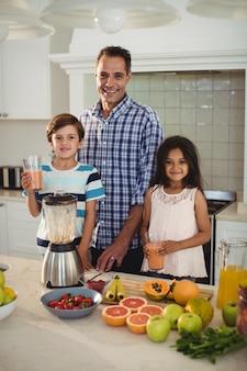 Porträt des vaters und der kinder, die glas smoothie halten