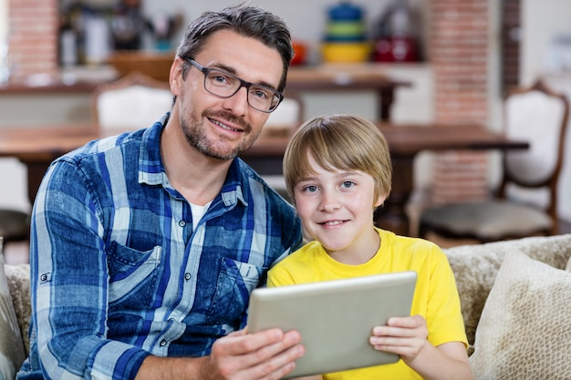 Porträt des vaters und des sohns, die digitale tablette im wohnzimmer verwenden