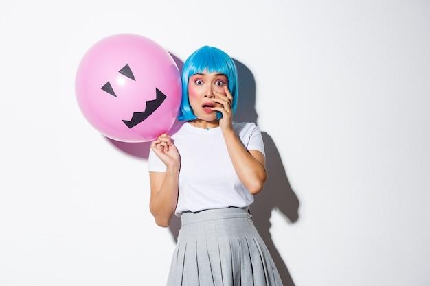 Porträt des verängstigten asiatischen mädchens im halloween-kostüm und in der blauen perücke, keuchend und überfallen, ballon mit unheimlichem gesicht haltend.