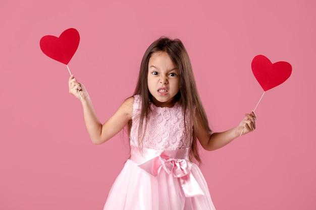 Porträt des verärgerten kleinen mädchens in einem rosa kleid, das papierherz hält