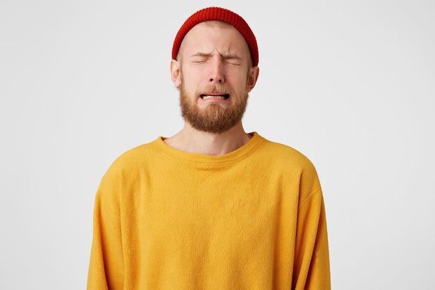 Porträt des verärgerten verzweifelten schluchzenden weinenden kerls