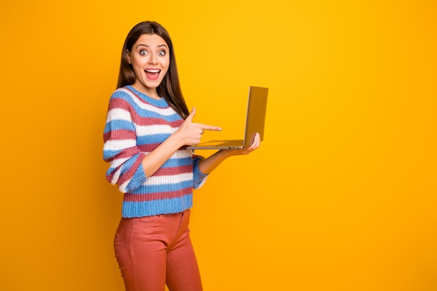 Porträt des verblüfften betäubten mädchens, das in den händen laptop direkten finger hält