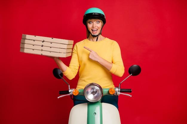 Porträt des verblüfften mädchens, das auf mopedfinger sitzt, der stapelstapelschachteln direkt demonstriert