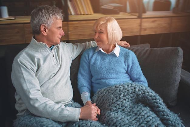 Porträt des verheirateten paares, das auf der couch sitzt