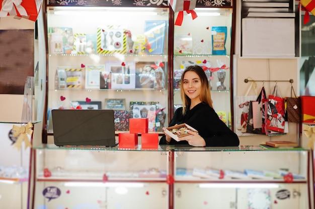 Porträt des verkäufers der jungen kaukasischen frau halten handgemachte kekse und süßigkeiten. kleines geschäft von süßigkeiten souvenirs shop.
