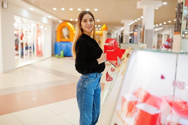 Porträt des verkäufers der jungen kaukasischen frau halten rote geschenkboxen. kleines geschäft von süßigkeiten souvenirs shop.