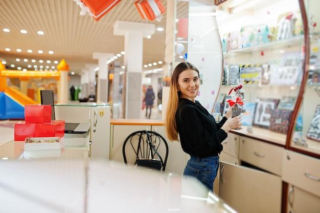Porträt des verkäufers der jungen kaukasischen frau. kleines geschäft von süßigkeiten souvenirs shop.