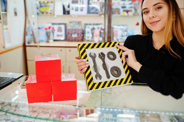 Porträt des verkäufers der jungen kaukasischen weiblichen frau halten satz mechanischer werkzeuge, die durch schokolade gemacht werden. kleines geschäft von süßigkeiten souvenirs shop. geschenk für echten mann.