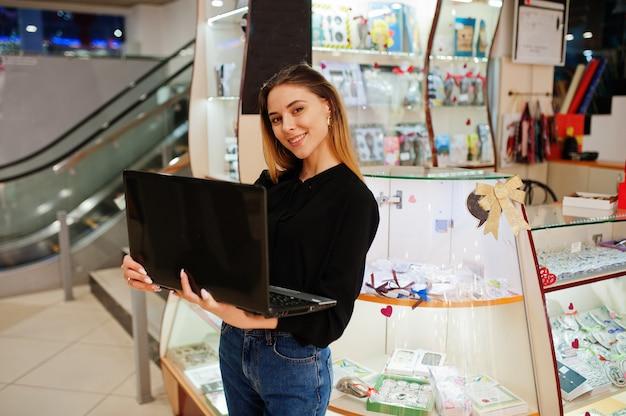 Porträt des verkäufers der jungen kaukasischen weiblichen frau unter verwendung des laptops. kleines geschäft von süßigkeiten souvenirs shop.