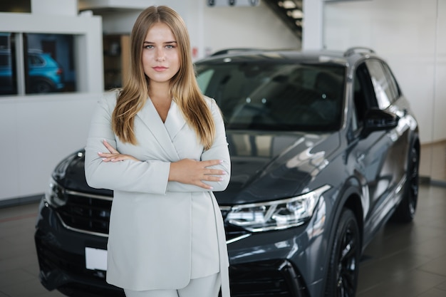 Porträt des verkäufers im autohaus attraktive junge frau steht vor dem auto