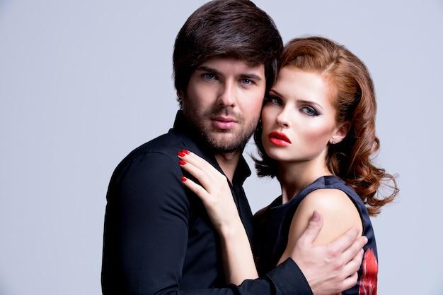 Porträt des verliebten glamourösen paares, das in der eleganzkleidung posiert