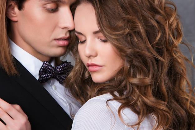 Porträt des verliebten jungen paares, das im studio in klassischer kleidung posiert