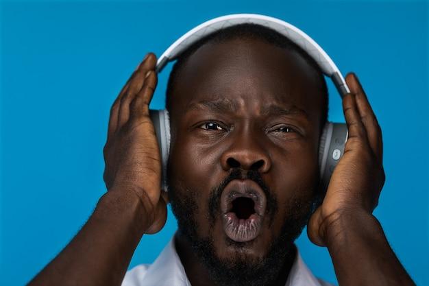 Porträt des verrückten mannes hörend musik in den kopfhörern