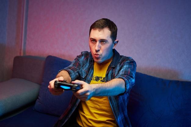 Porträt des verrückten verspielten spielers, junge, der genießt, videospiele drinnen zu spielen, die auf dem sofa sitzen und das konsolenspielfeld in den händen halten. zu hause ausruhen, ein schönes wochenende haben