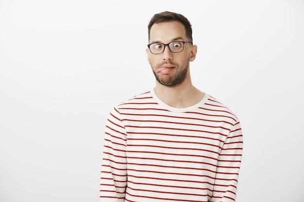 Porträt des verspielten lustigen kerls mit der borste in der schwarzen brille, die zunge herausstreckt und nase betrachtet
