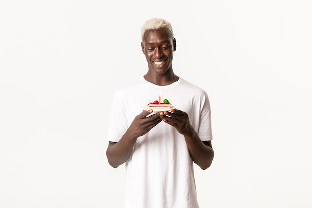 Porträt des verträumten, glücklichen blonden afroamerikanischen kerls, der geburtstagstorte betrachtet und lächelt und wunsch am b-tag macht