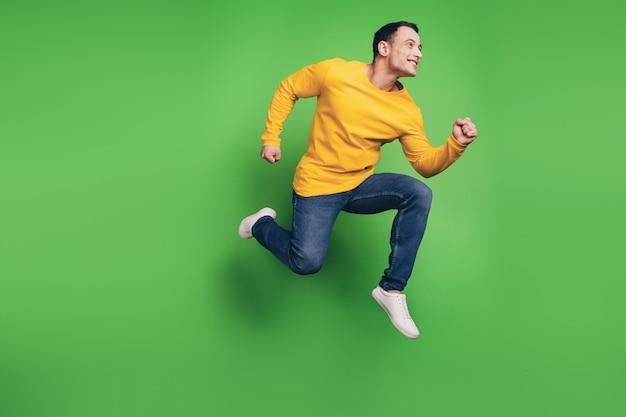 Porträt des verträumten gutaussehenden kerls, der fliege springt, genießen sie den schnellen lauf auf grünem hintergrund