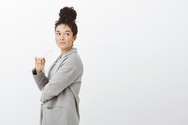 Porträt des verträumten gutaussehenden unternehmers im stilvollen grauen mantel mit brötchenfrisur, der mit leichtem glücklichem lächeln rechts schaut und brille in der hand hält