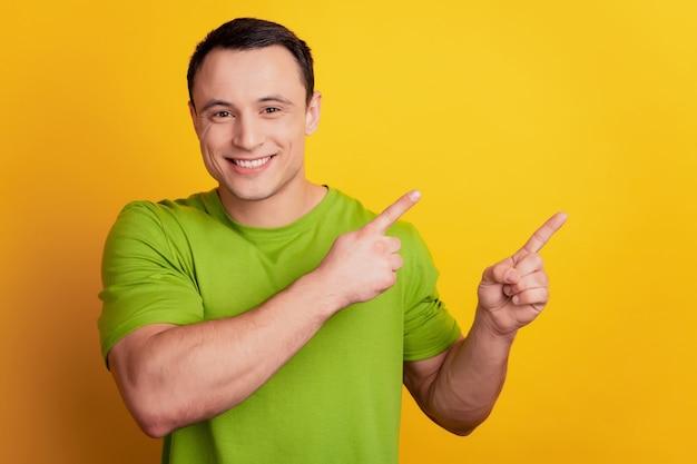 Porträt des verträumten kerls zeigen zeigefinger-leerraum-neuheitsverkaufskonzept auf gelbem hintergrund