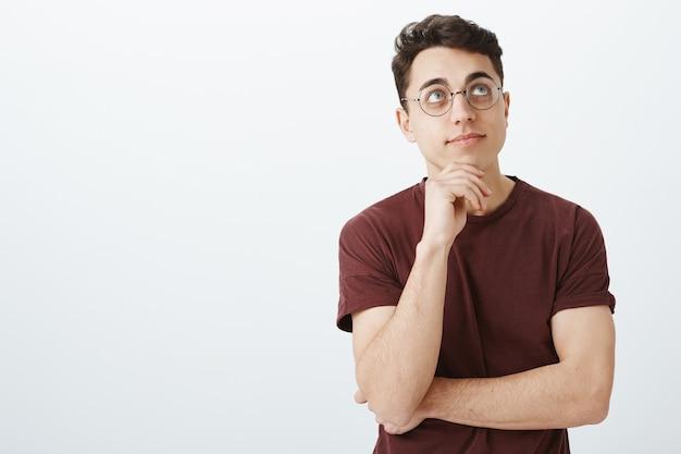 Porträt des verträumten kreativen geschäftsmannes im roten t-shirt und in den runden gläsern