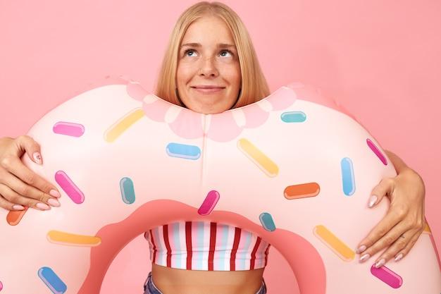 Porträt des verträumten niedlichen blonden teenager-mädchens in der sommerkleidung, die isoliert mit rosa schwimmring in form des donuts aufwirft, schaut auf und träumt von ferien auf dem seeweg
