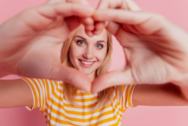 Porträt des verträumten romantischen mädchenherzgesten-abdeckungsgesichtes auf rosa hintergrund